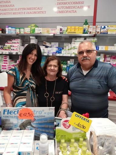 tre persone dietro il bancone di una farmacia