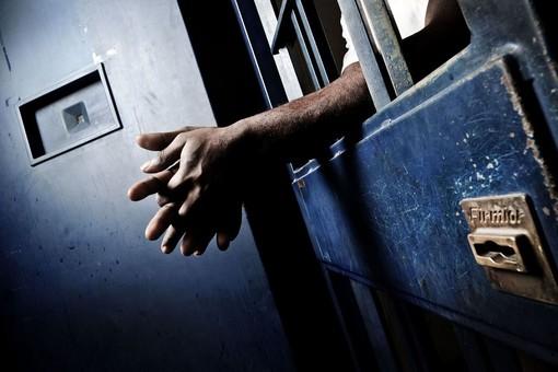 Mani e braccia che sporgono da una cella