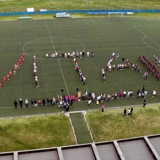 Persone schierate a formare una scritta su un campo di calcio