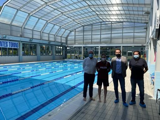 tre persone in una piscina al coperto a bordo vasca