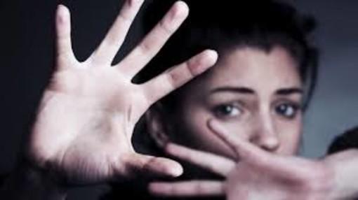 Donna che si ripara con le mani e sguardo spaventato